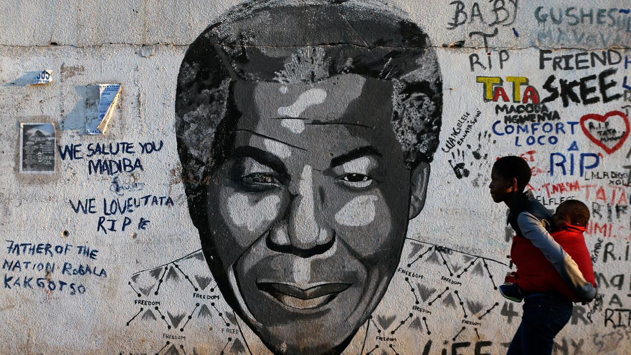 A woman carrying a child on her back walks past a mural showing former South African president Nelson Mandelas face at Katlehong township, South Africa, Saturday, July 18, 2015.
