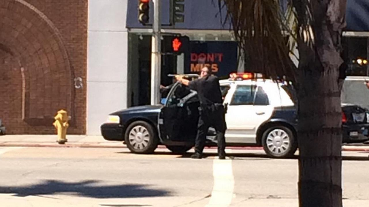 A police officer draws his gun on Ventura Boulevard near Laurel Canyon Boulevard in Studio City on Friday, July 24, 2015.