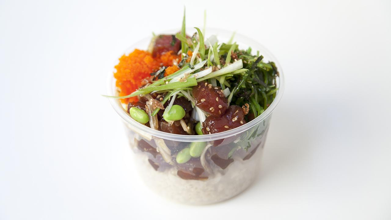 An order of sweet unagi sauce poke on a bed of rice with seaweed salad, edamame and masago.