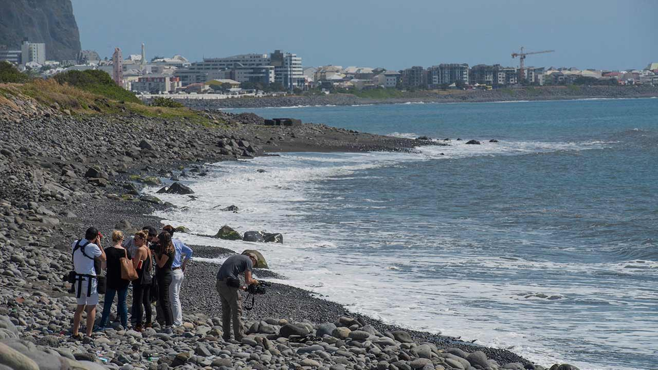 Workers search the beach for additional airplane debris near the shore where an airplane wing part was washed up on the Indian Ocean island of Reunion Sunday, Aug. 2, 2015.