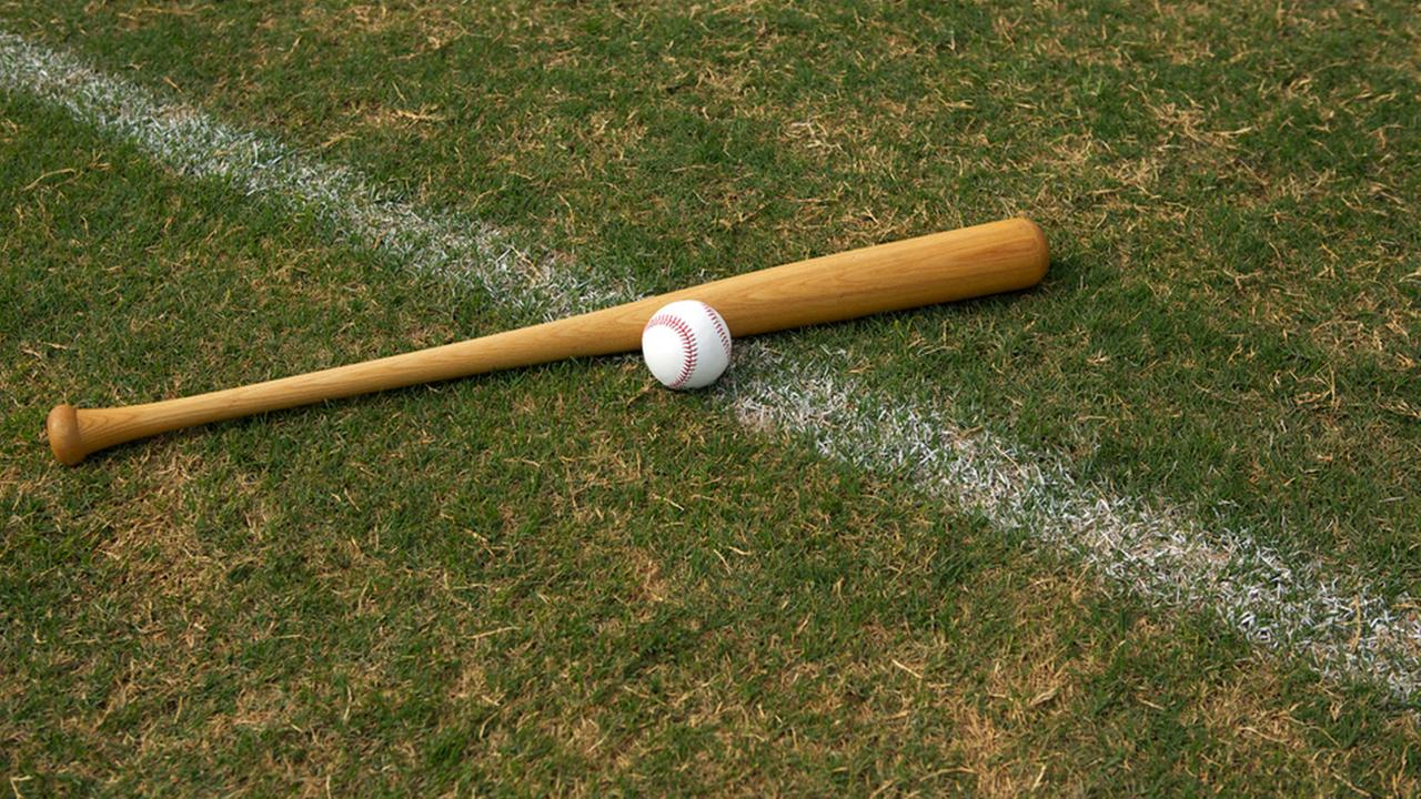A baseball bat and baseball are shown on a field in an undated photo.