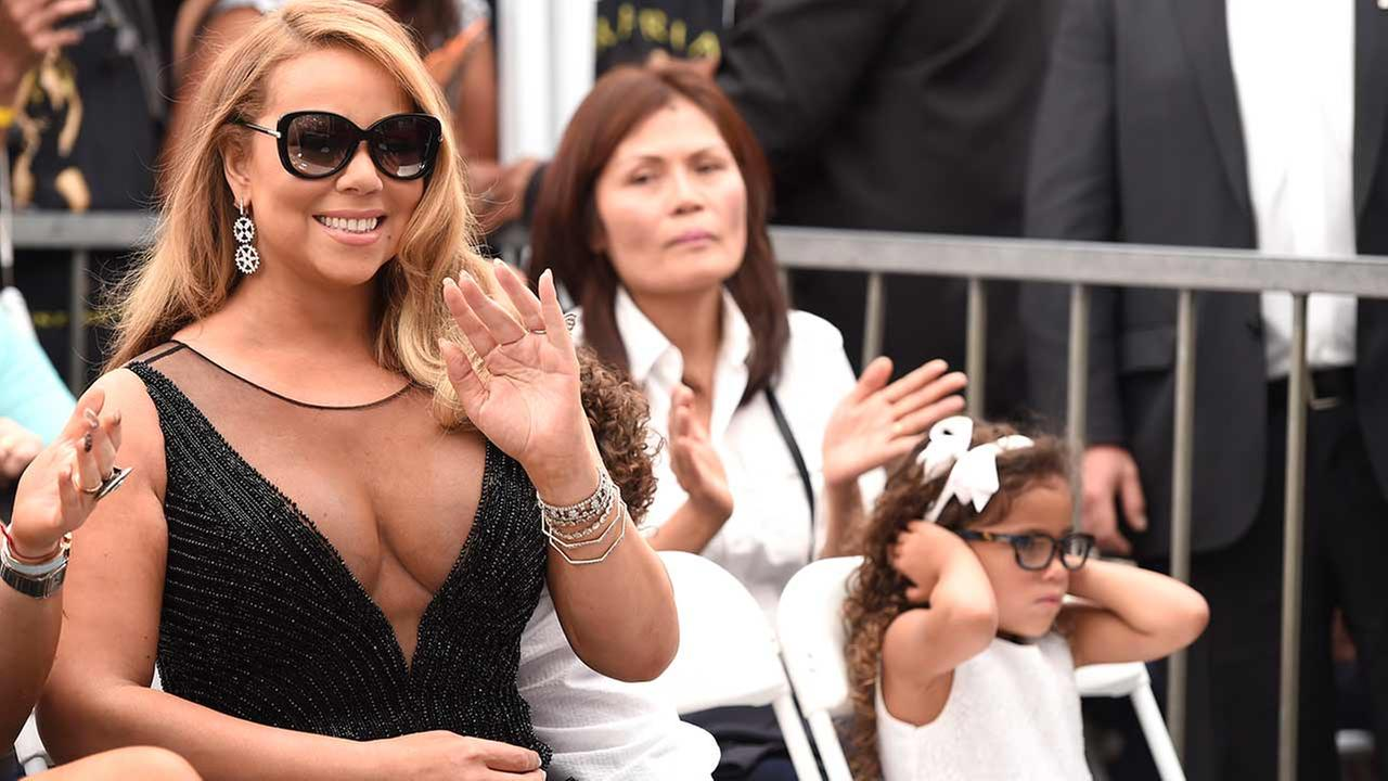 Mariah Carey, left, waves while her daughter blocks her ears at a ceremony honoring Carey with a star on the Hollywood Walk of Fame on Wednesday, Aug. 5, 2015 in Los Angeles. Chris Pizzello/Invision/AP