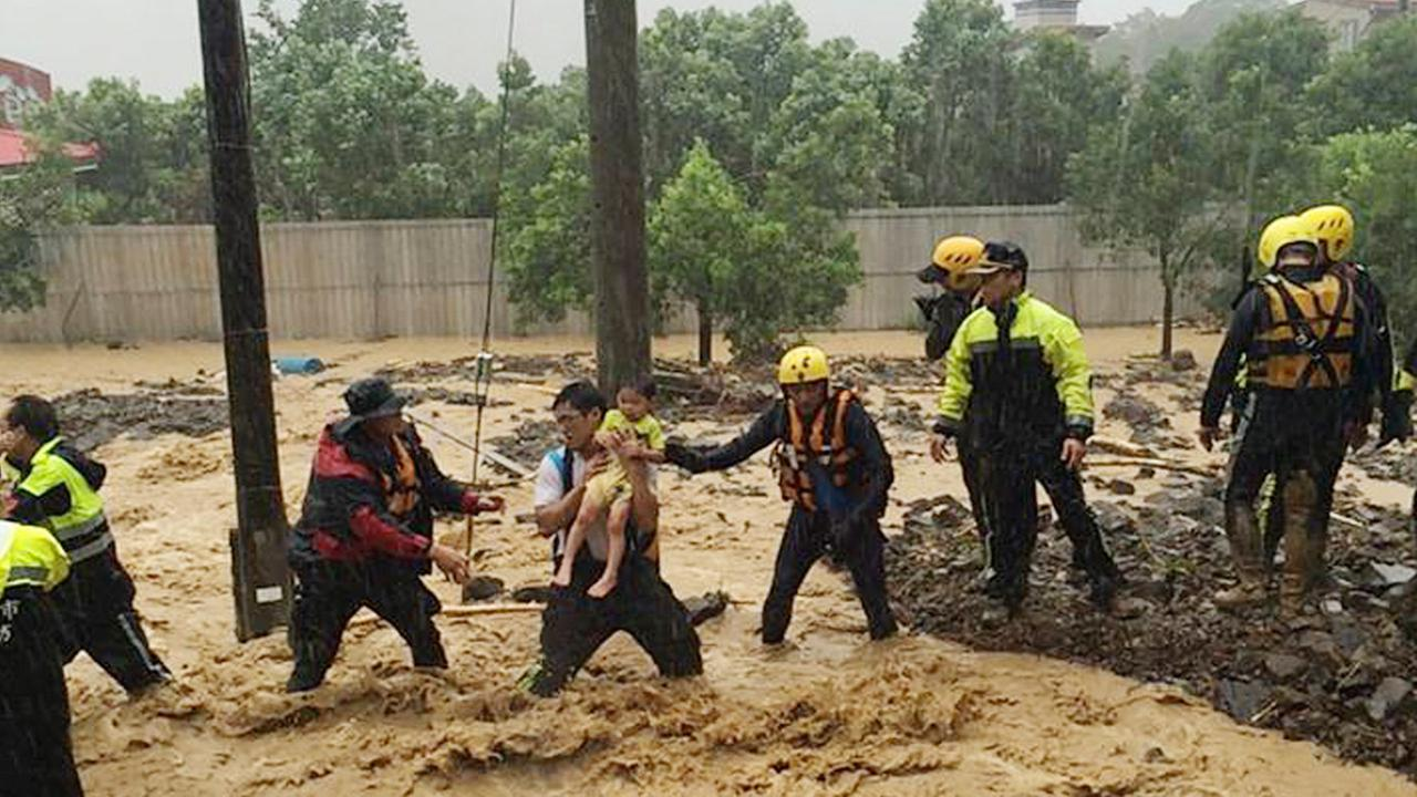 Emergency rescue personnel carry a child through a flash mudslide caused by Typhoon Soudelor in Xindian, New Taipei City, northern Taiwan, Saturday, Aug. 8, 2015.