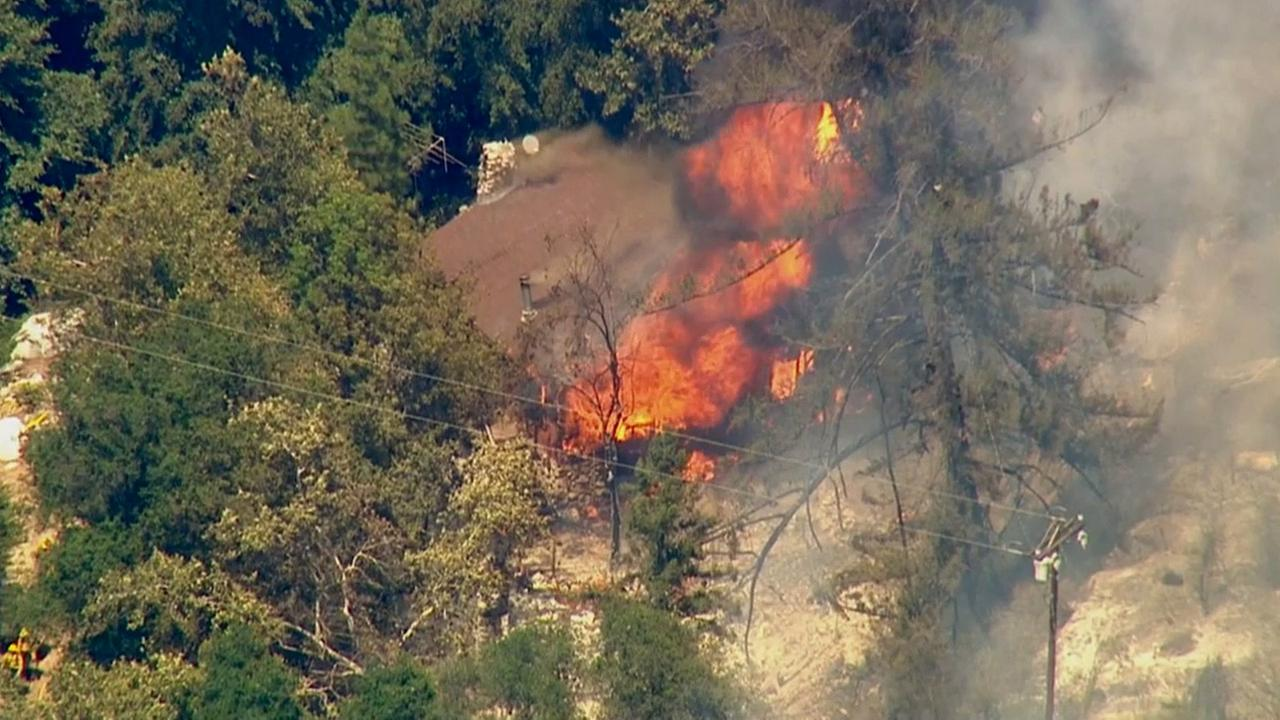 Flames engulf a cabin after a brush fire broke out in a hillside north of Glendora on Friday, Aug. 14, 2015.