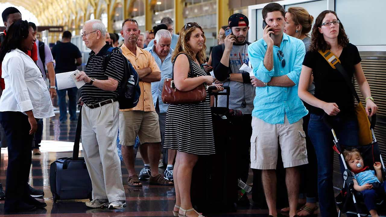 People stand in line at Washingtons Reagan National Airport after technical issues at a Federal Aviation Administration center in Virginia caused delays on Saturday, Aug. 15, 2015.