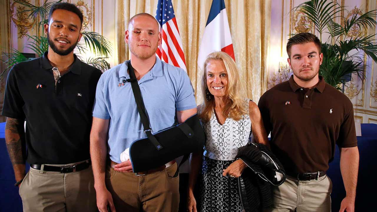 Anthony Sadler, left, U.S. National Guardsman, right, and U.S. Airman Spencer Stone, second from left, pose for photographers at the U.S. Ambassadors residence in Paris, France.