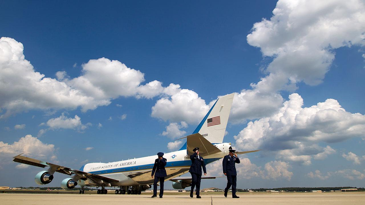 Military personnel hold their hats as Air Force One, with President Obama aboard, departs on Aug. 24, 2015, en route to the National Clean Energy Summit.