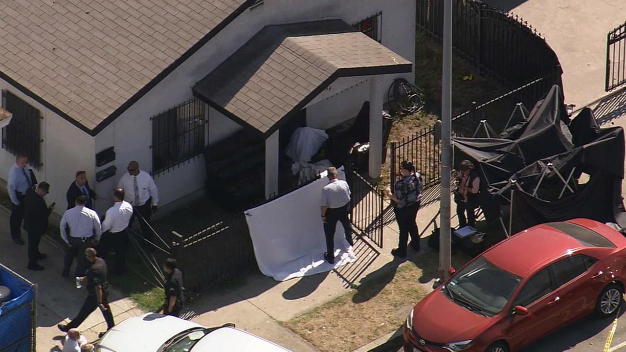 Los Angeles police investigate the shooting deaths of two men in South Los Angeles on Wednesday, Aug. 26, 2015.