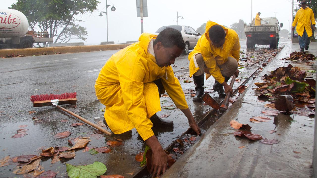 Workers clean highway gutters as Tropical Storm Erika approaches Santo Domingo, in the Dominican Republic, Friday, August 28, 2015.
