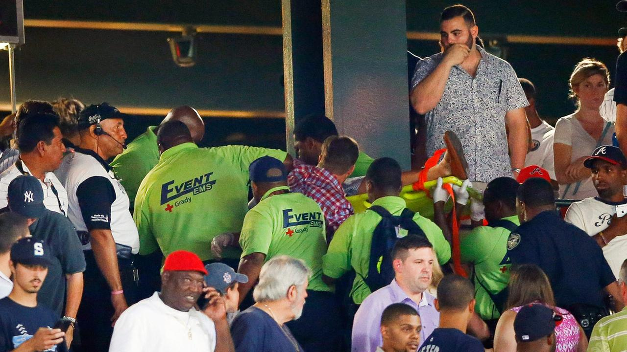 Emergency medical personnel carry an injured fan from the stands at Turner Field during a baseball game between Atlanta Braves and New York Yankees Saturday, Aug. 29, 2015.