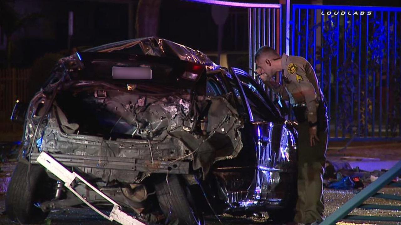 A law enforcement officer examines a mangled car following a chase and crash in Lynwood on Wednesday, Sept. 2, 2015.