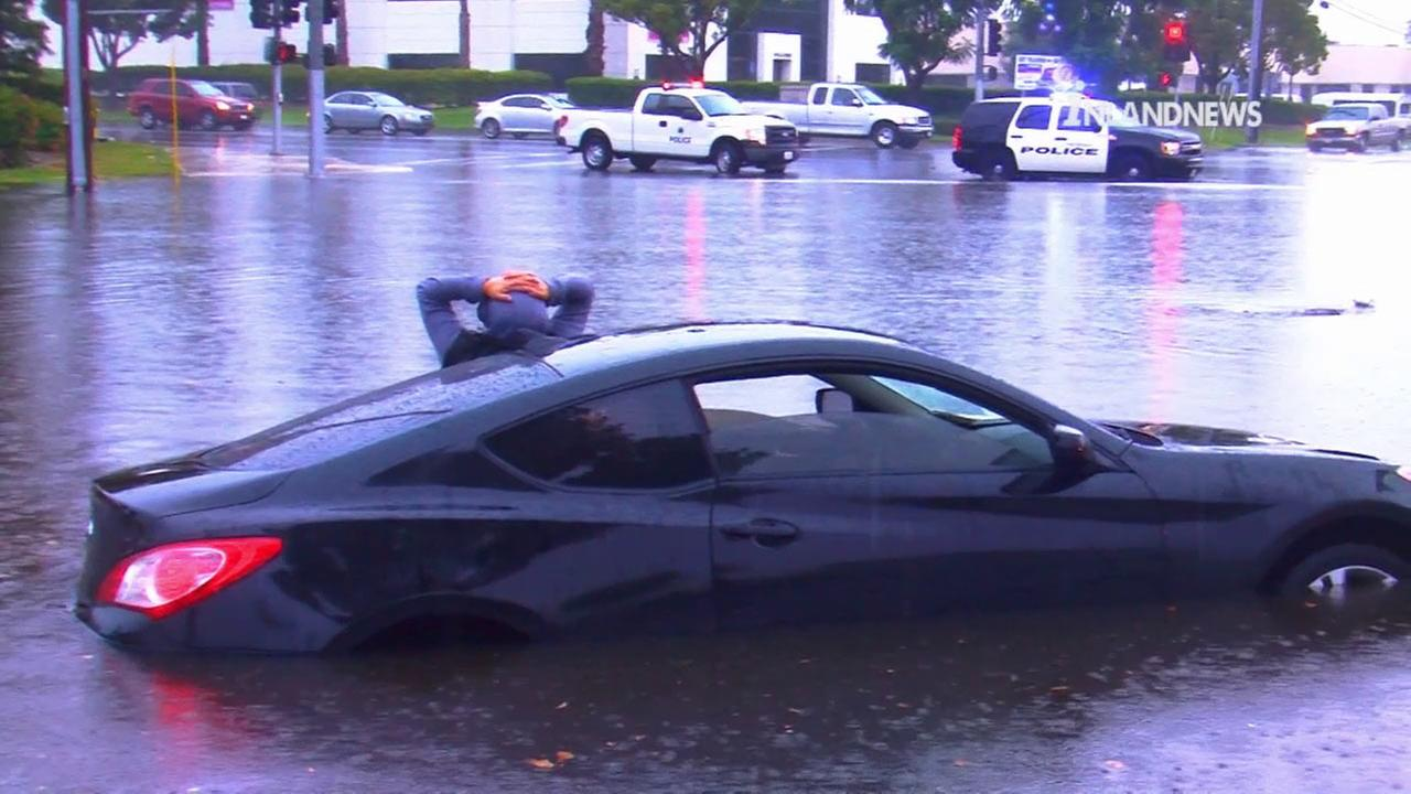 A driver waits for help after his car got stuck on a flooded street in Ontario on Tuesday, Sept. 15, 2015.