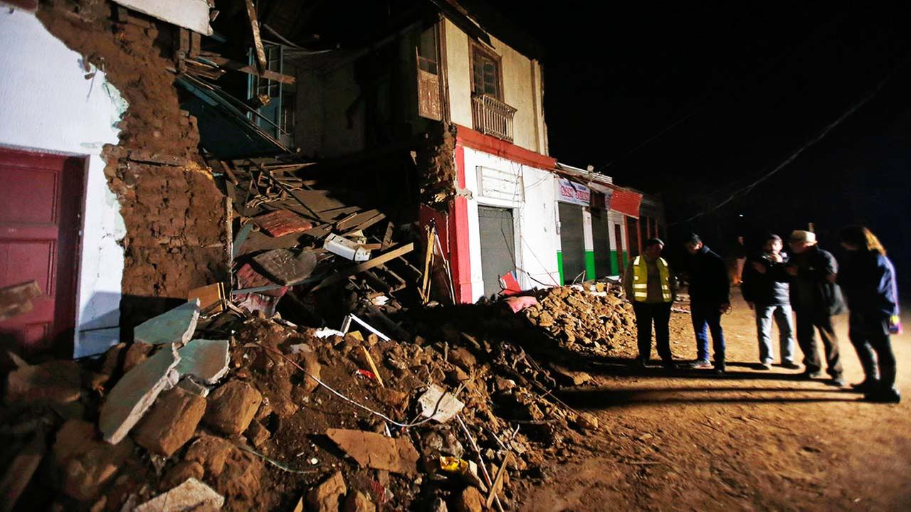 People stand outside a destroyed house in Illapel, Chile, Thursday, Sept. 17, 2015 following a magnitude-8.3 earthquake on Wednesday night.