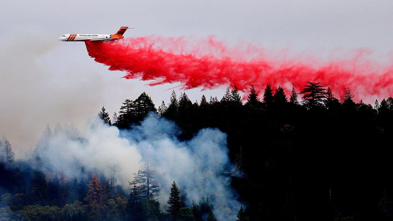 A firefighting plane drops a load of fire retardant over a smoldering hillside Tuesday, Sept. 15, 2015, in Middletown, Calif.