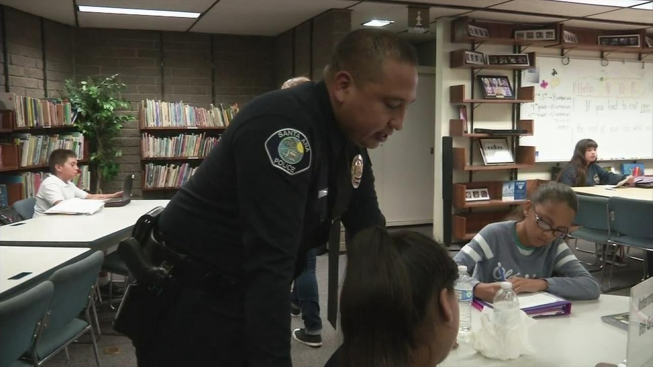 A Santa Ana police officer is helping a student study at the PAAL after school program on Friday, Oct. 2, 2015.