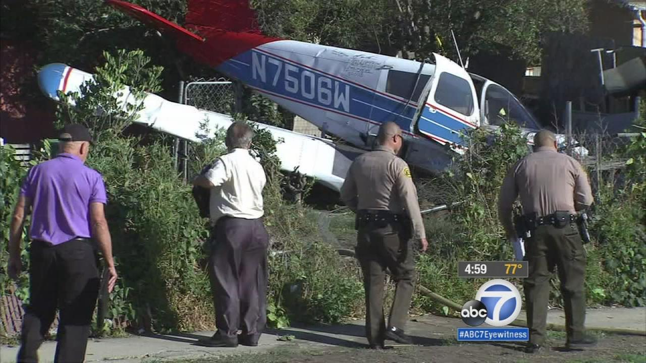 Authorities investigate the scene of a single-engine plane crash in the backyard of a Compton home on Wednesday, Oct. 7, 2015.