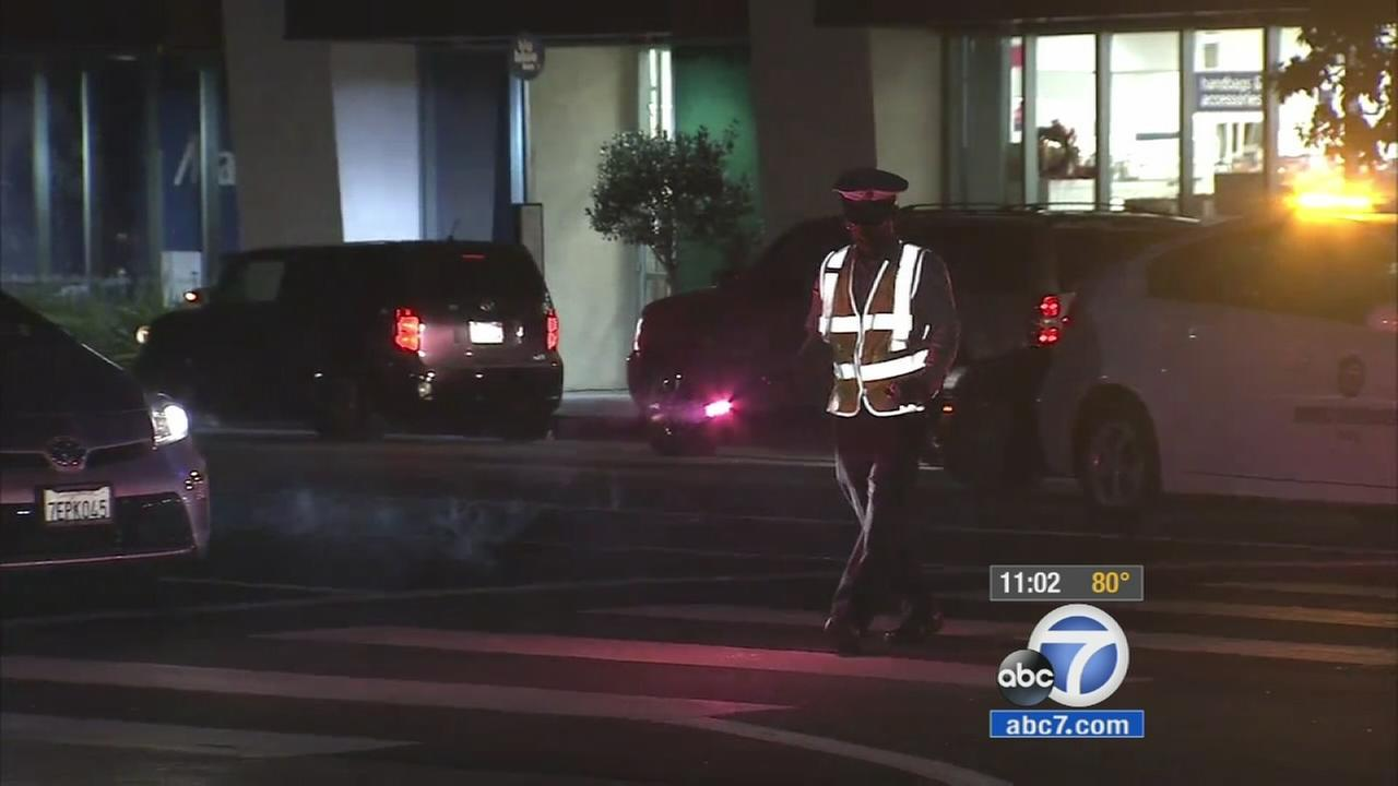 A Los Angeles Department of Water and Power crew member walks across the street in reflective gear after the power is out in West L.A. on Saturday, Oct. 10, 2015.