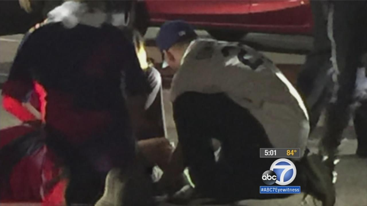 Bystanders help an injured man outside Dodger Stadium on Friday, Oct. 9, 2015.