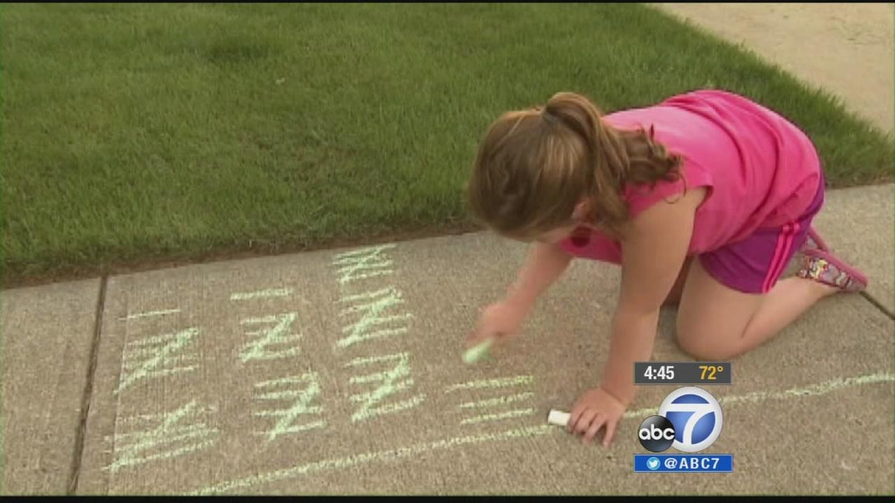 A girl draws tally marks with sidewalk chalk in this undated file photo.