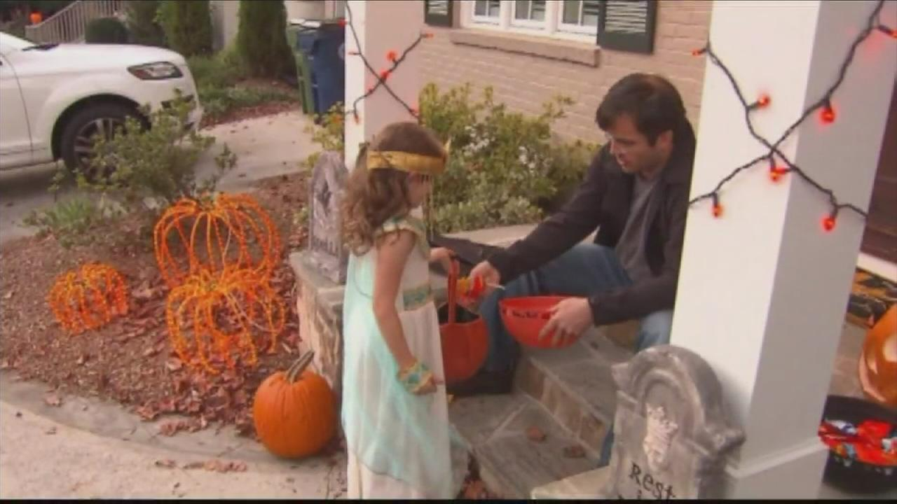 A parent hands out candy to a child in costume on Halloween in an undated file photo.