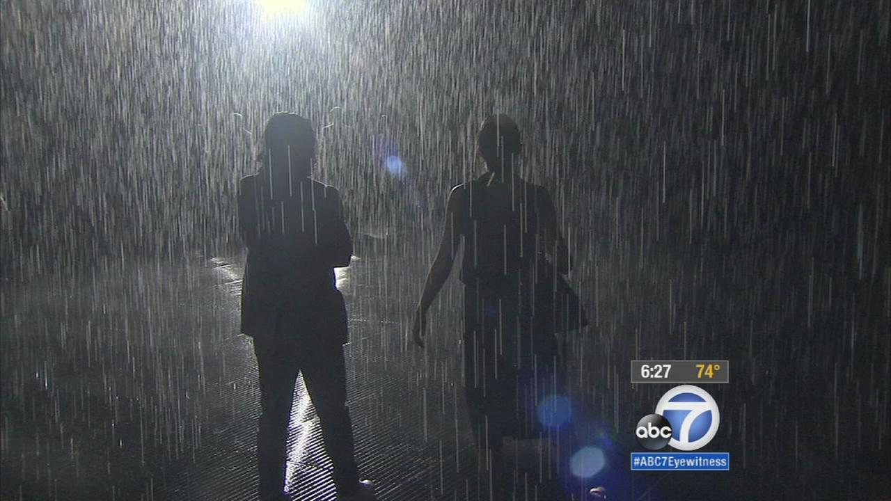 Two visitors walk through the LACMA Rain Room during a preview event on Wednesday, Oct. 28, 2015.