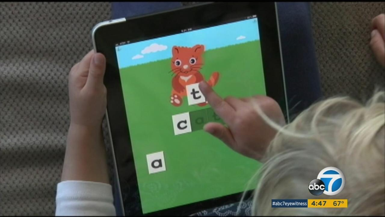 A toddler uses a tablet to play a spelling game in an undated photo.