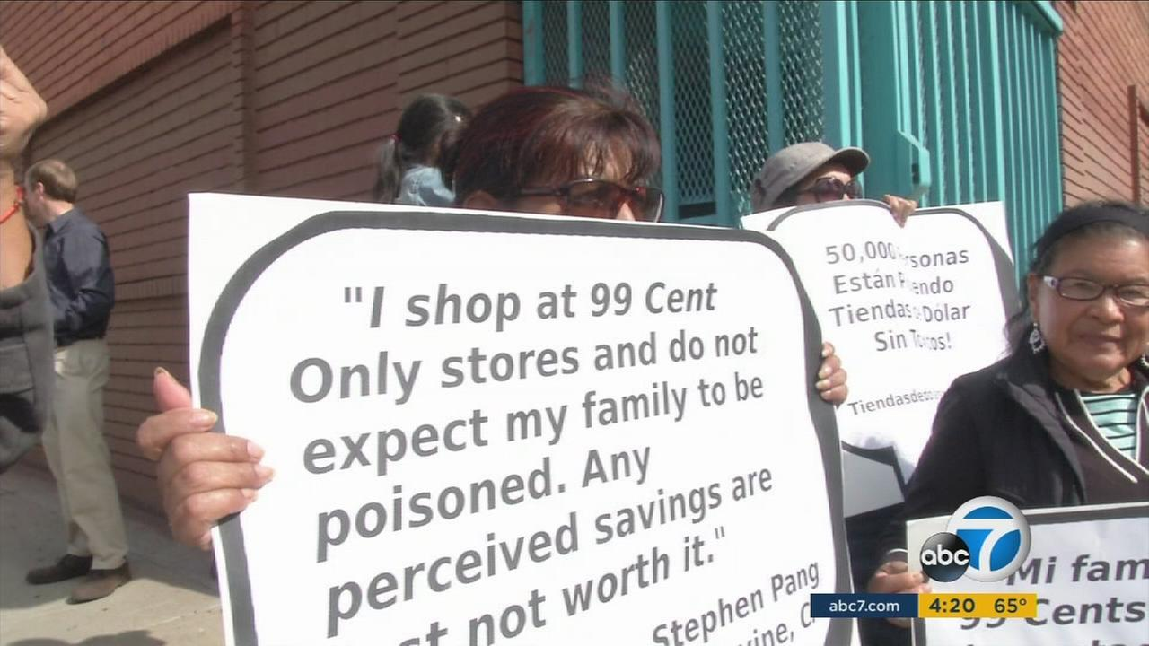 A concerned customer holds up a sign urging the 99 Cents Only Stores to stop carrying items made with toxic chemicals.