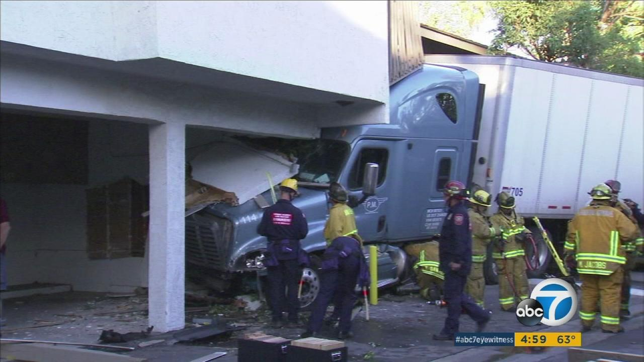 Firefighters evaluate the damage done to an apartment building after a big rig slammed into it in Garden Grove on Monday, Nov. 9, 2015.
