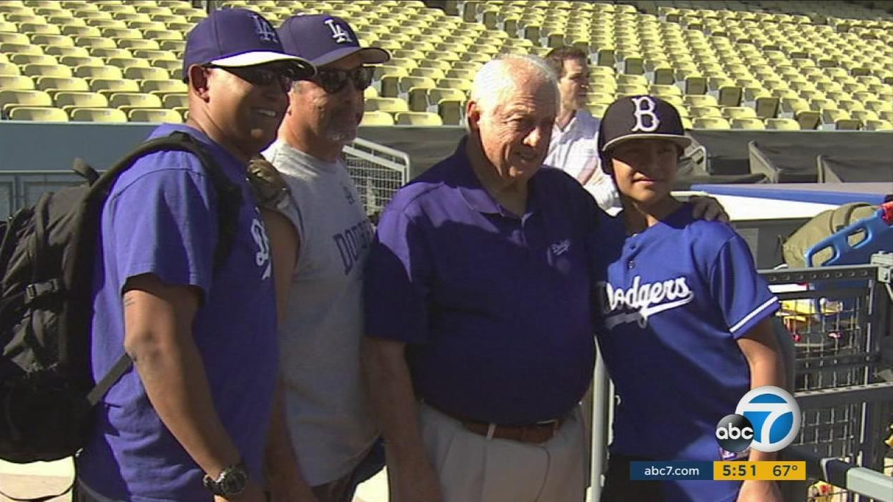 Fans pose with former Dodgers manager Tommy Lasorda as the team honored veterans and active military on Wednesday, Nov. 18, 2015.