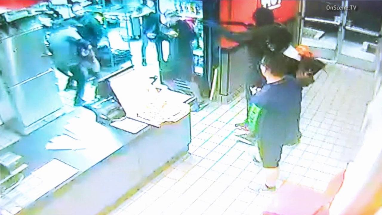 This surveillance still image shows armed suspects holding up a Pizza Hut restaurant in Buena Park on Sunday, Nov. 29, 2015.