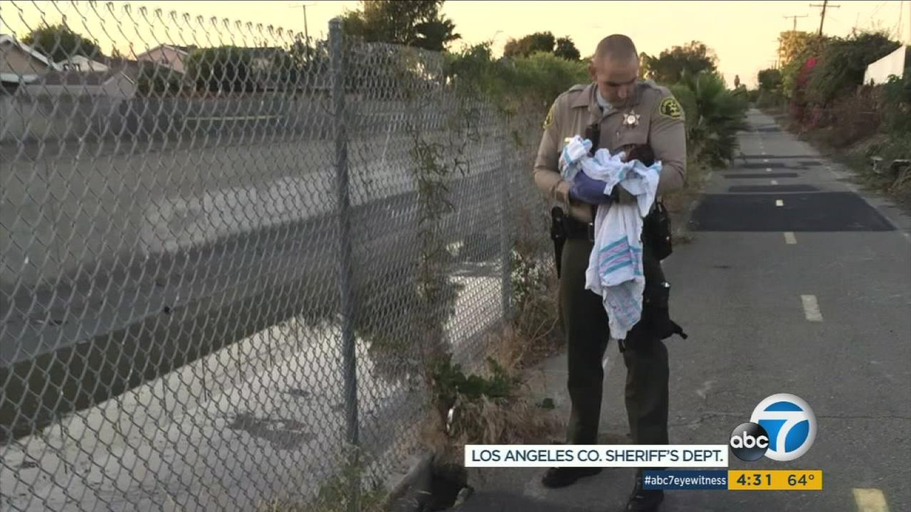 Los Angeles County Sheriffs Deputy Adam Collette holds a baby girl saved from a hole along a bike path in Compton on Friday, Nov. 27, 2015.