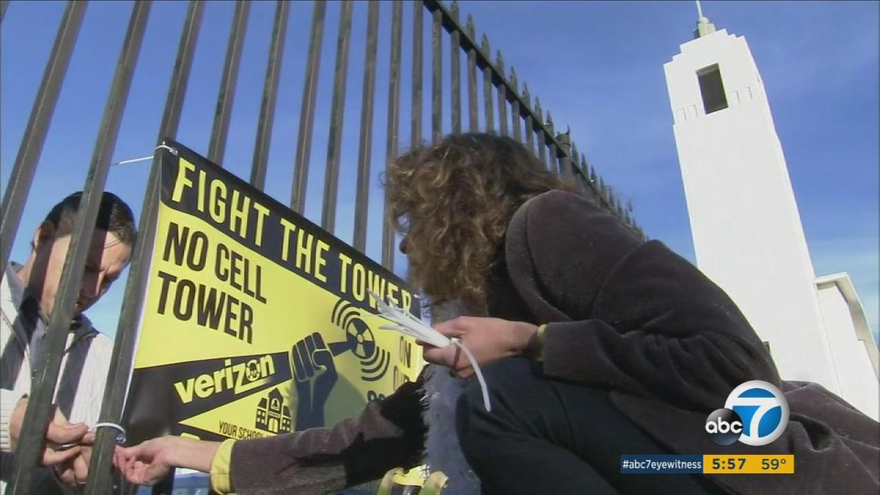Parents post signs opposing a cell tower that may be installed in a church bell tower, which is next to Larchmont Charter School in West Hollywood.