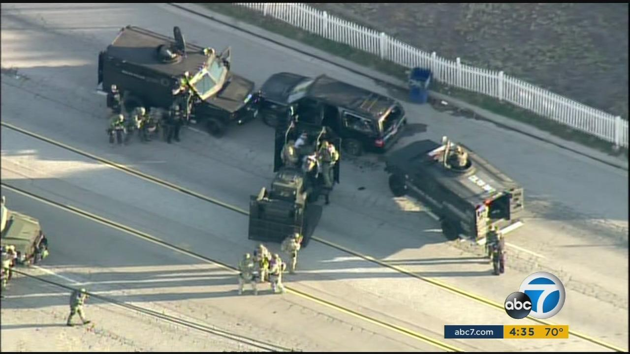 SWAT and other law enforcement agencies surround the SUV driven by the two suspects accused in the San Bernardino mass shooting on Wednesday, Dec. 2, 2015.