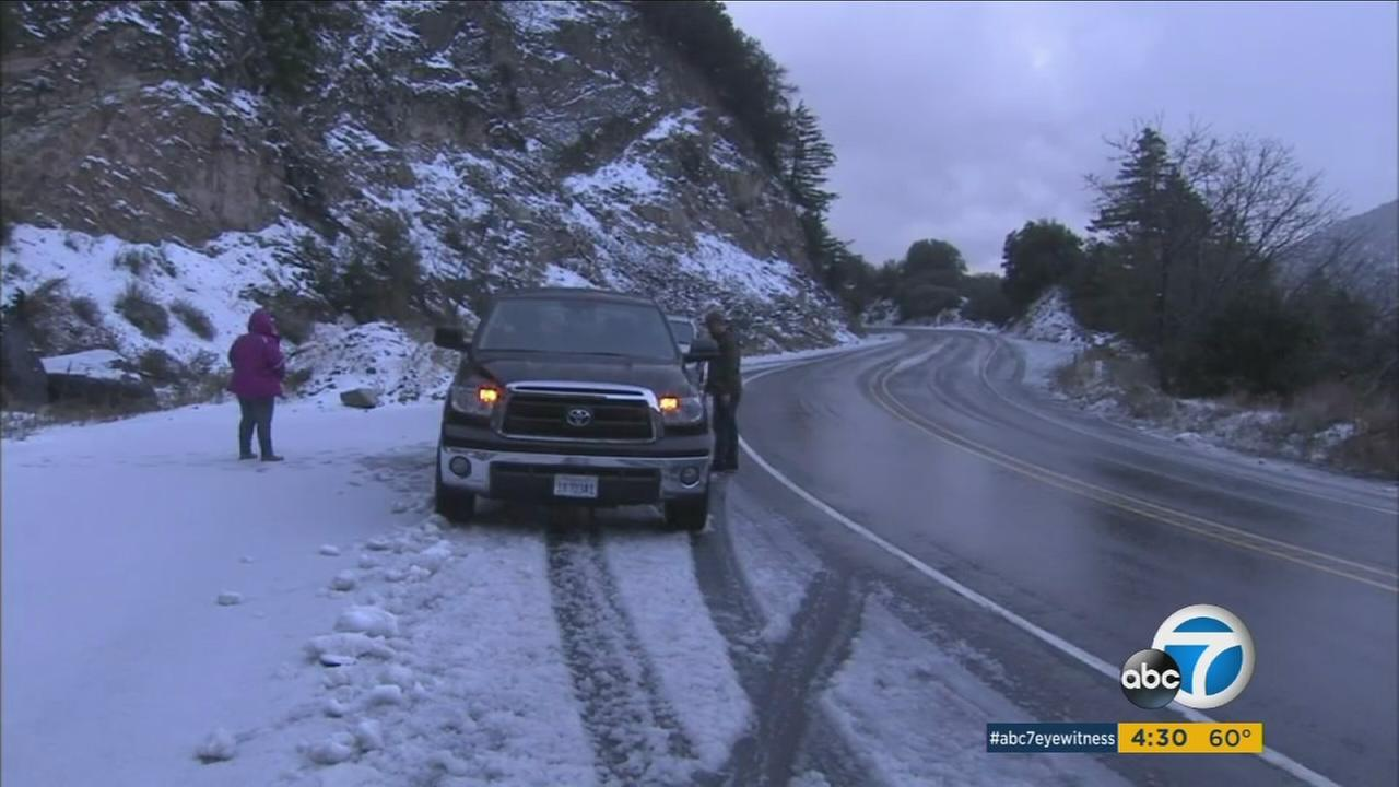 Residents pull over to look at the snow on a road in the Inland Empire on Friday, Dec. 11, 2015.