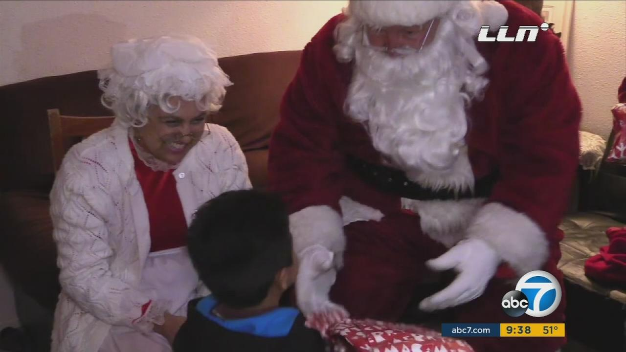 Santa and Mrs. Clause give a child a present in Jurupa Valley.