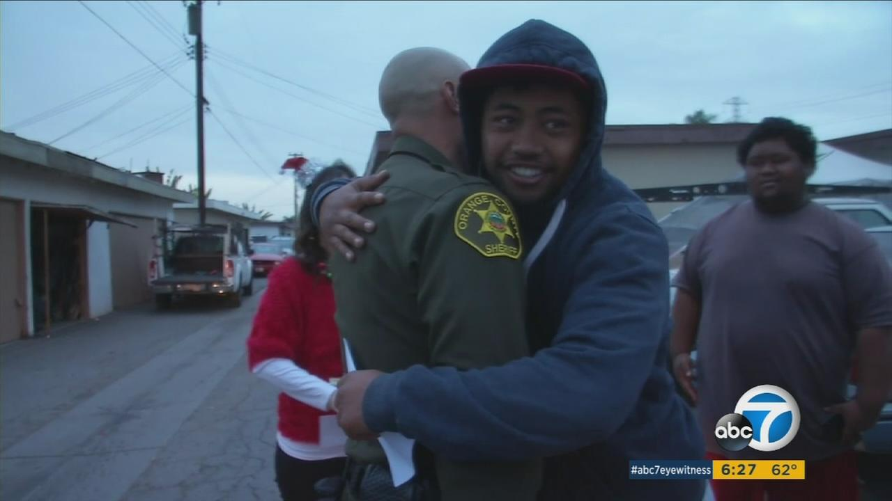 An Orange County Sheriffs deputy is hugged after surprising a resident with $100 donated by an anonymous person.