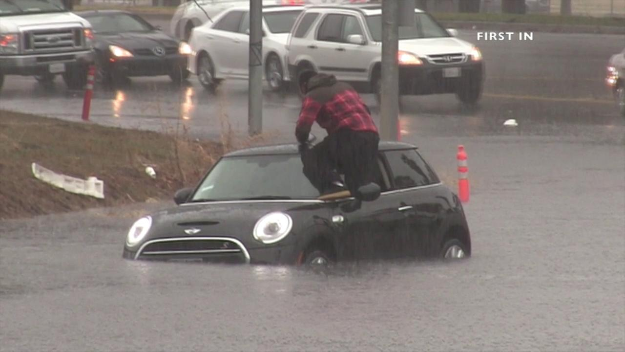 A man climbs out of his car and jumps to safety after flood waters overtake a Los Angeles street on Tuesday, Jan. 5, 2016.