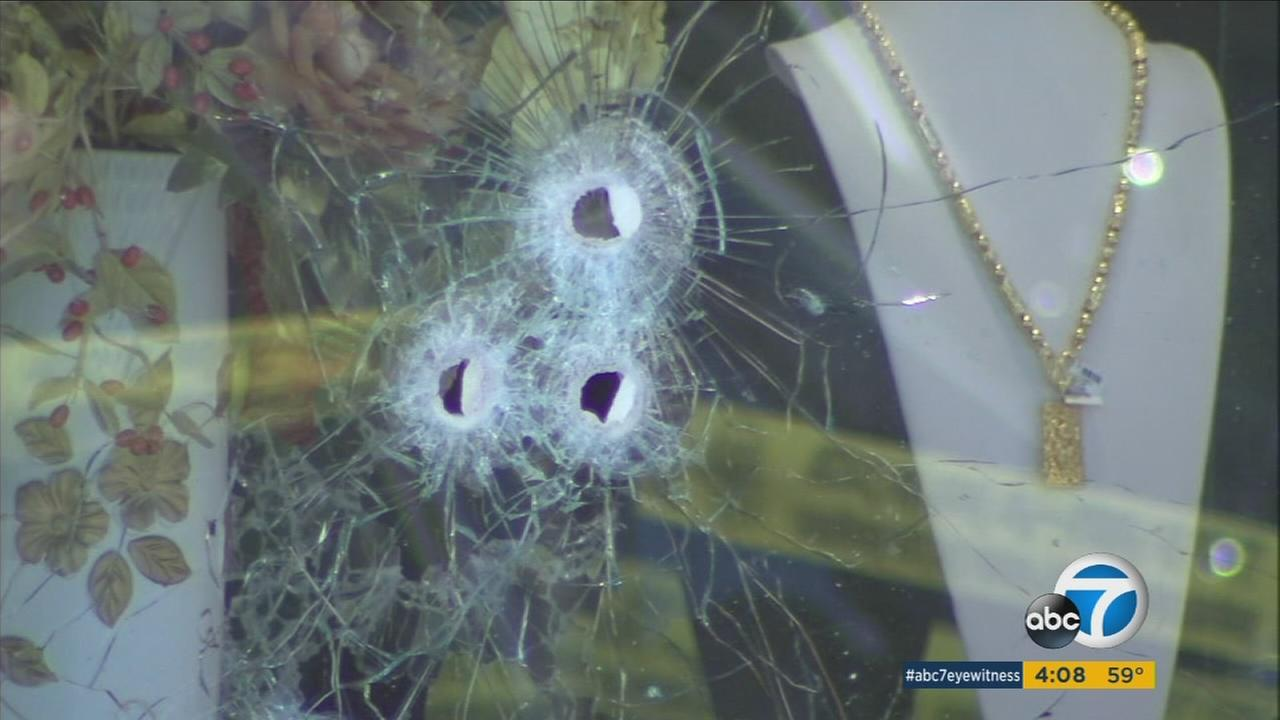Bullet holes in the window of a jewelry store are shown on Thursday, Jan. 7, 2016.