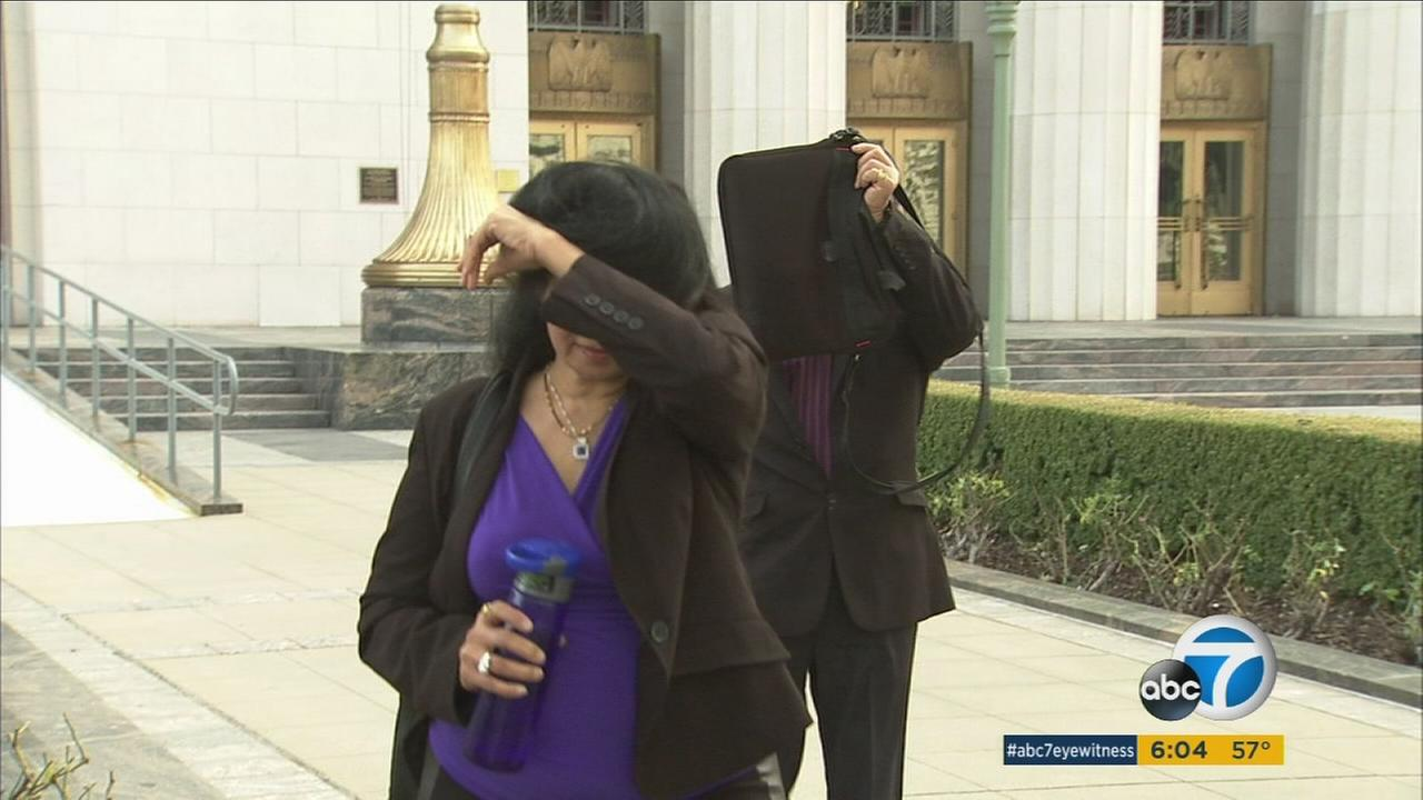 Nisha and Ajit Bhargava shield their faces as they walk out of an L.A. court on Monday, Jan. 12, 2016, after pleading guilty to a scheme of setting up sham marriages for pay.
