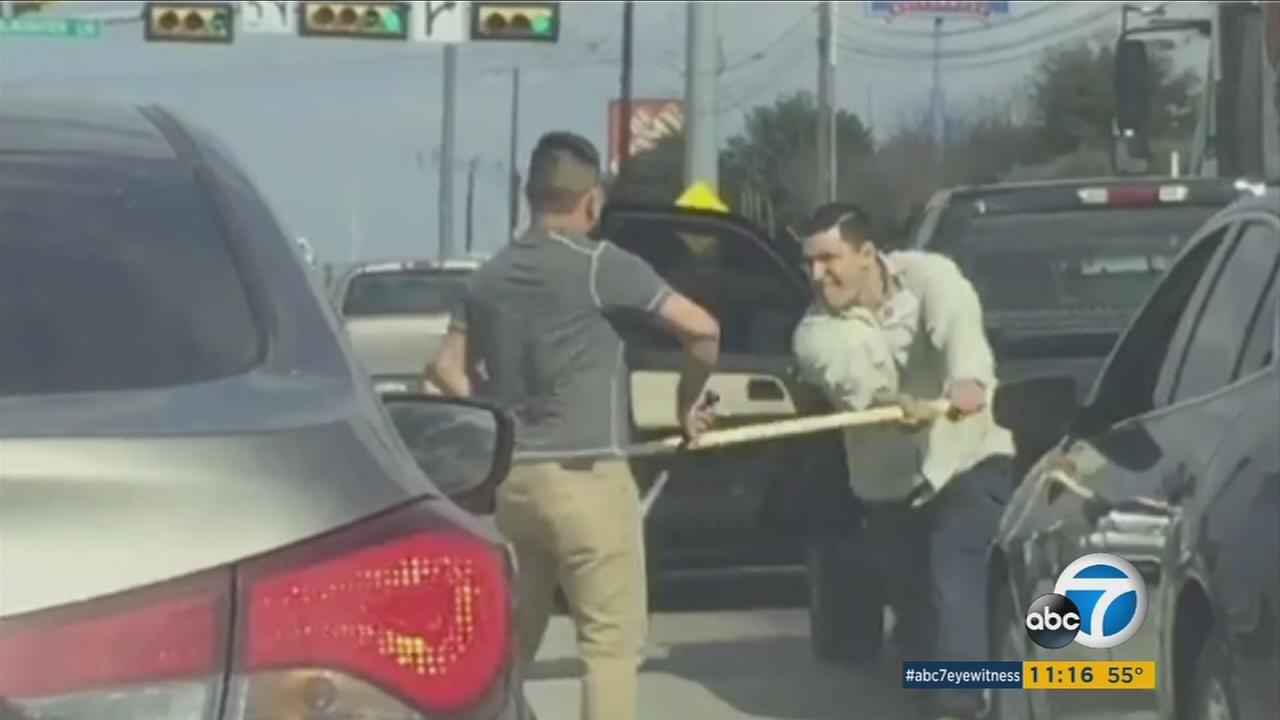 Two drivers seen wielding weapons at each other while in traffic in Austin,Texas.