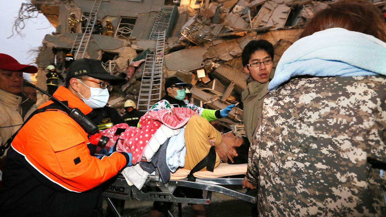 Rescue workers carry a man from the site of a toppled building after an earthquake in Tainan, Taiwan, Saturday, Feb. 6, 2016.