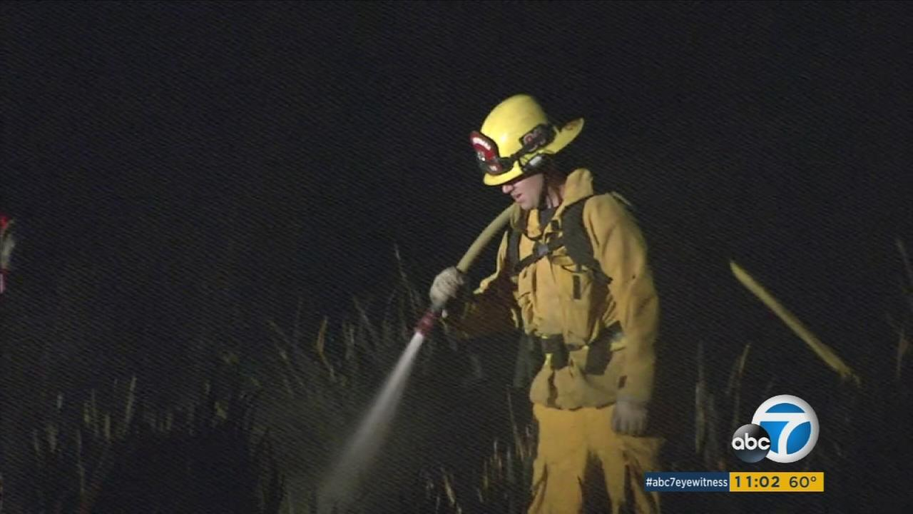 A firefighter puts out hot spots in Camarillo after a small brush fire breaks out on Sunday, Feb. 7, 2016.