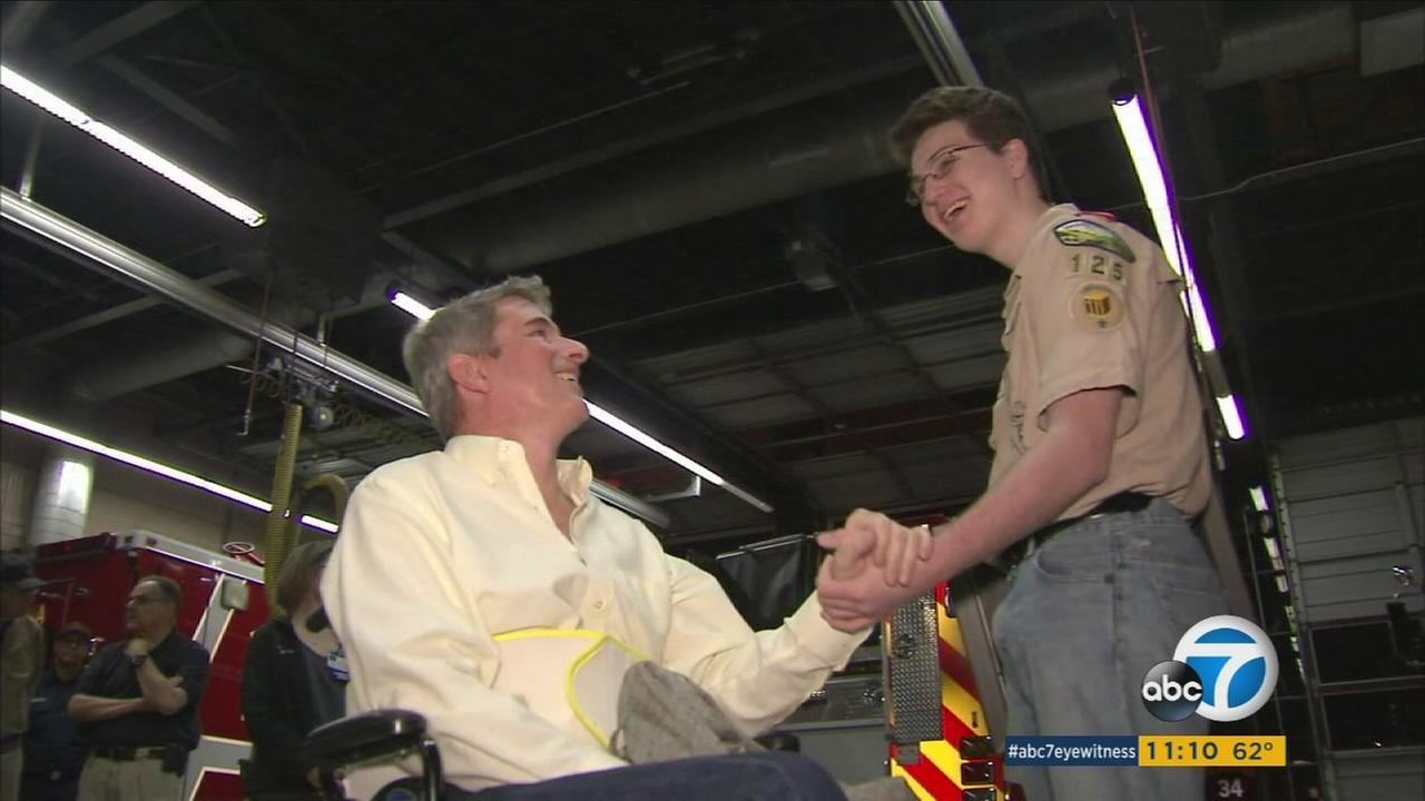 John Hall and his son Evan hold hands during a ceremony in Pasadena to honor Evans brave actions when John suffered a stroke.