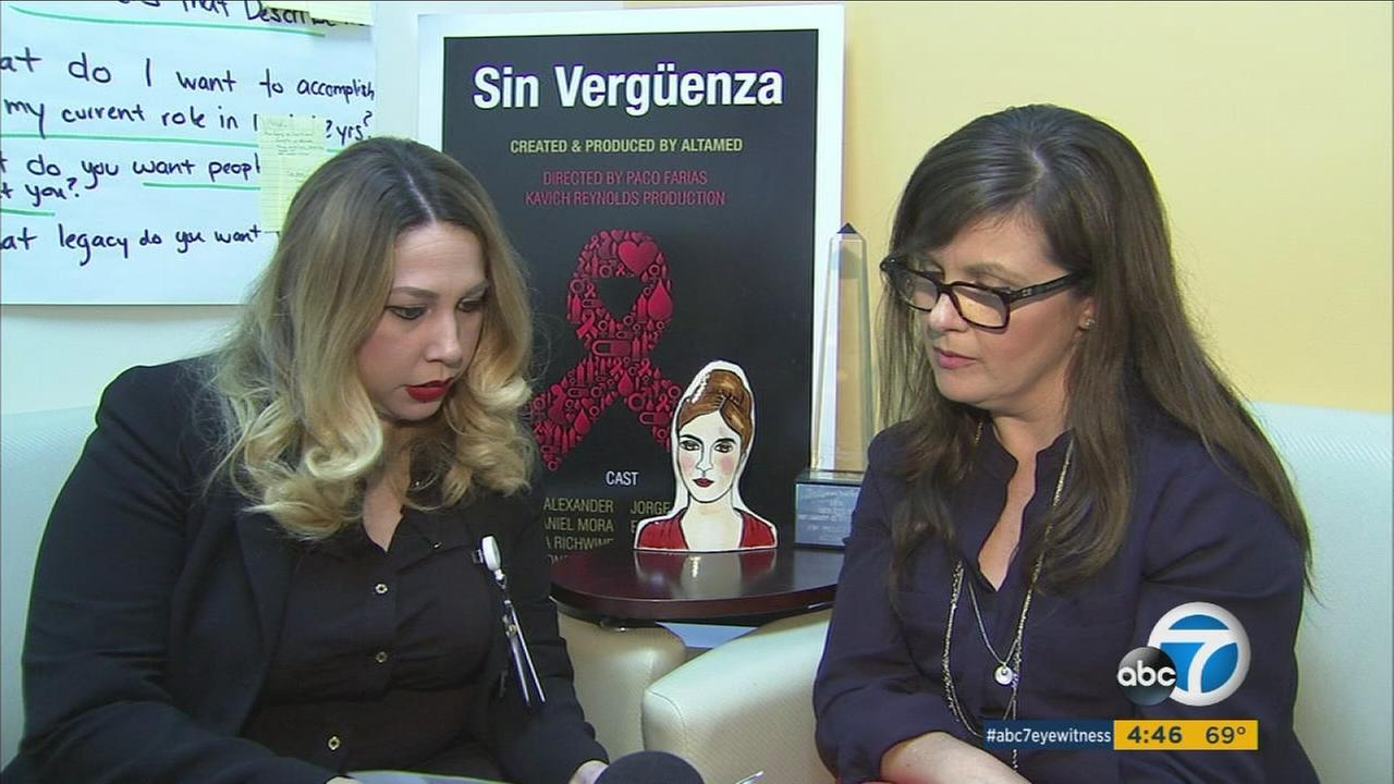 Two health care workers sit in front of an advertisement for the televnovela they developed called Sin Verguenza.