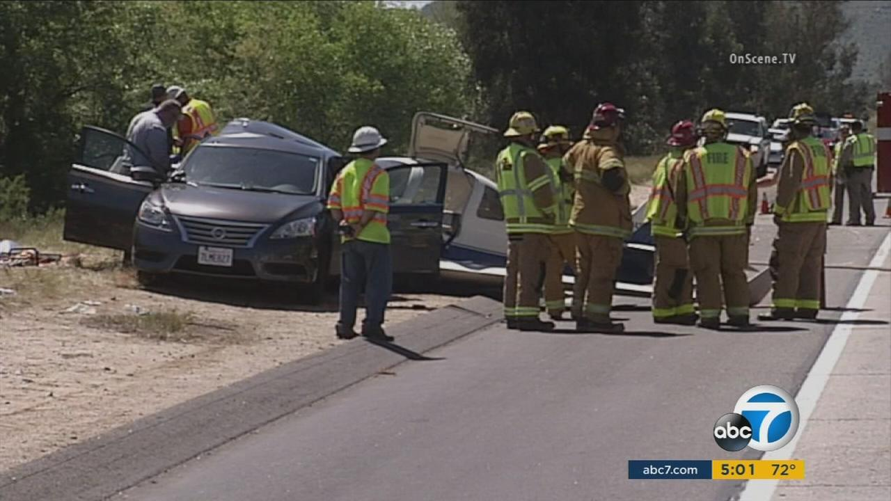One person was killed and five others injured after a small plane crashed and struck a car on the northbound 15 Freeway in San Diego County Saturday morning.