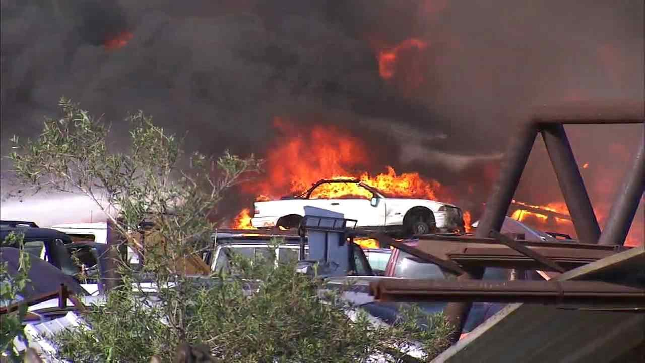 Cars are seen engulfed in flames after a fire broke out at a junkyard in Sun Valley on Sunday, April 17, 2016.