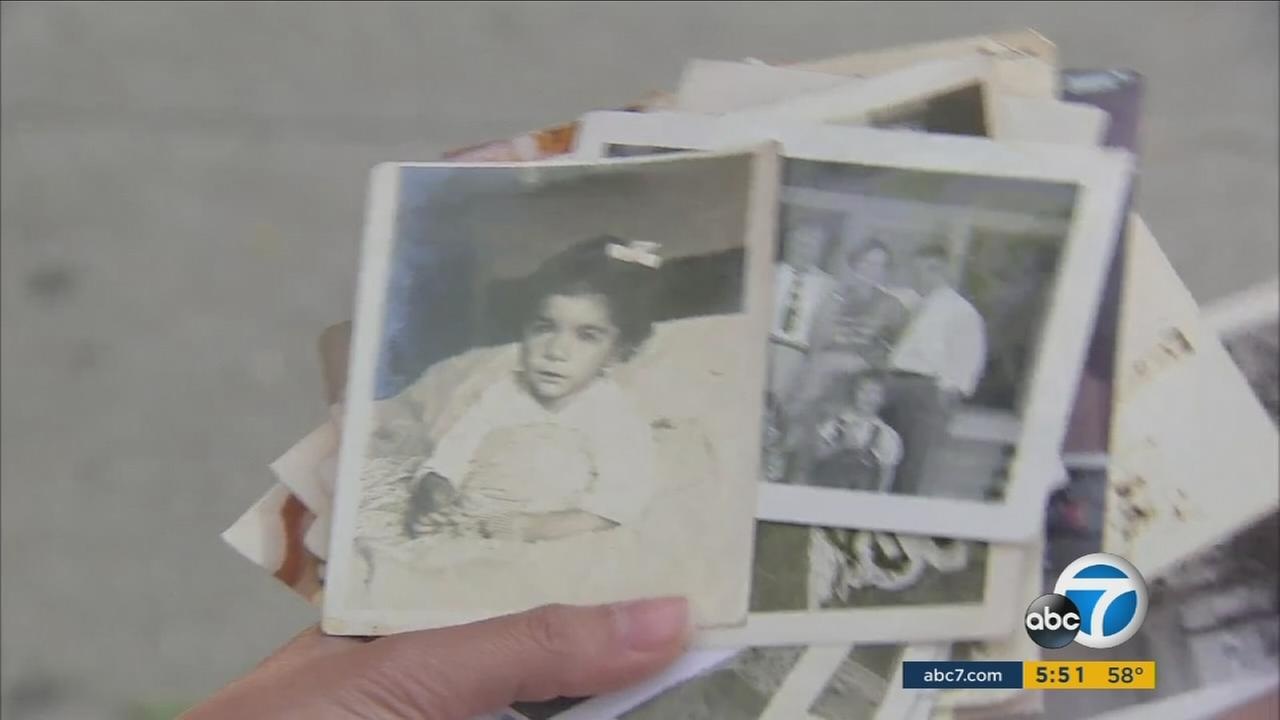 A woman who is searching for the owner of a pile of pictures found on a bench in Santa Monica holds the family photos in her hand.