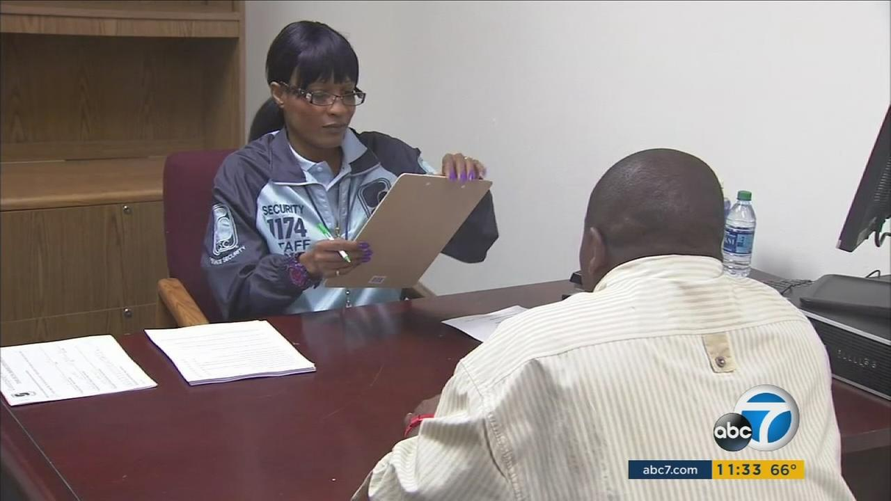 A woman helps a Los Angeles resident fill out an employment form for a chance to work at the Los Angeles Rams home games.