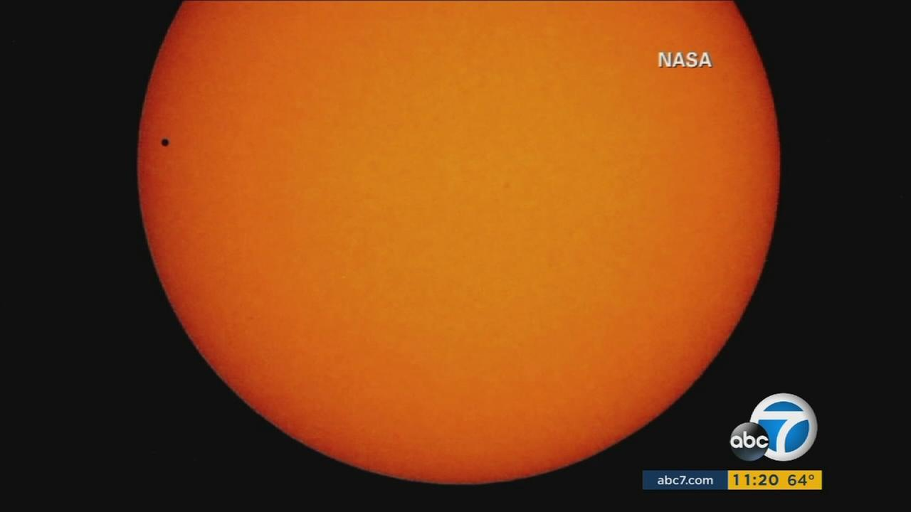 Mercury, resembling a tiny black dot, is seen as it passes directly between the Earth and the sun.