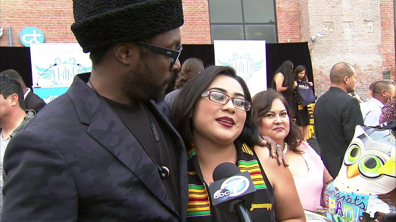 Musician will.i.am stands by Theodore Roosevelt High School graduate Cynthia Erenas on graduation day.